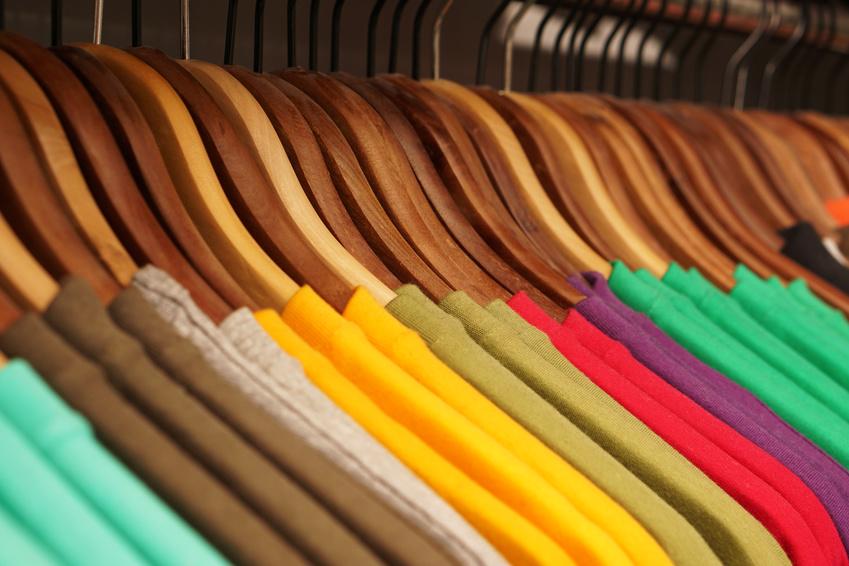 Bunte T-Shirts auf braunen Kleiderbügeln
